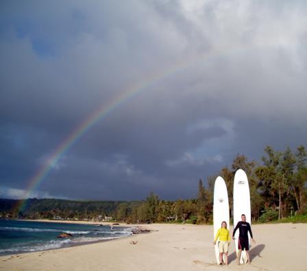 Karen with her surf instructor under a rainbow